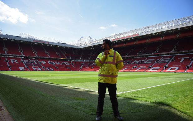 A security guard stands at the empty stadium after a EPL match was called off due to a bomb scare.