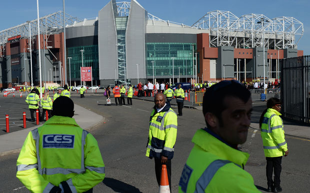 Event staff stand outside the evacuated Old Trafford stadium in Manchester, England on May 15, 2016.