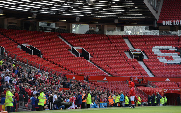 The Stretford End is pictured empty following the evacuation of both the Sir Alex Ferguson stand (unseen) and the Stretford stands ahead of the English Premier League football match between Manchester United and Bournemouth at Old Trafford in Manchester, north west England, on May 15, 2016.