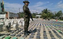 A Colombian police officer standing guard over eight tons of seized cocaine in Turbo, Antioquia department, on May 15, 2016.