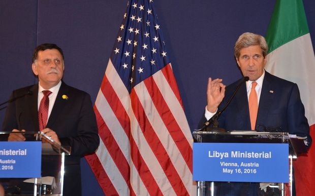 Prime Minister of Libya Fayez al-Sarraj  stands by as US Secretary of State John Kerry delivers a speech after the ministerial meeting on Libya in Vienna, Austria.