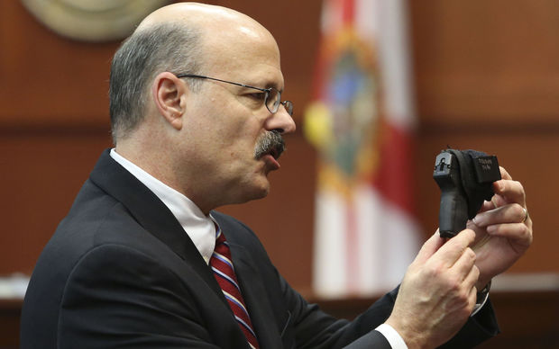 Assistant state attorney Bernie de la Rionda as he shows George Zimmerman's gun to the jury while presenting the state's closing arguments against Zimmerman during his trial in Seminole circuit court in Sanford, Florida.