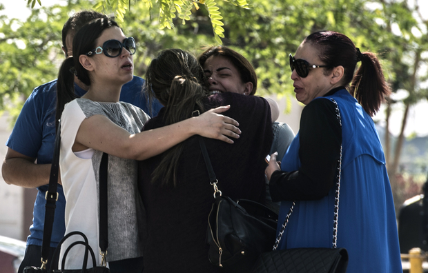 Families of passengers who were flying in an EgyptAir plane that vanished from radar en route from Paris to Cairo react as they wait outside a services hall at Cairo airport.