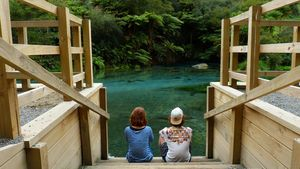 Two young Dutch tourists sit on some wooden steps that lead to the clear blue/green water at Blue Spring, Putaruru