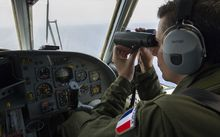 The French Navy (Marine Nationale) on May 22, 2016, shows a French soldier aboard an aircraft looking through binoculars during searches for debris from the crashed EgyptAir flight MS804 over the Mediterranean Sea.