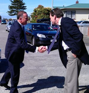 John Key greets the families' lead solicitor Colin Smith before the meeting.