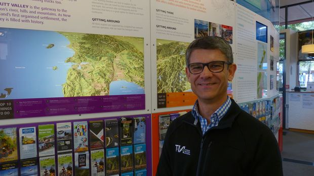 Chris Roberts the Chief Executive of Tourism Industry Aotearoa at the iSITE in Wellington. He is surrounded by New Zealand maps and tourist leaflets