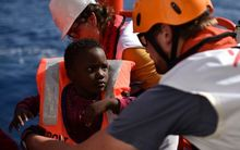 Rescuers take care of a child during a rescue operation at sea of migrants and refugees on May 24, 2016 in the Mediterranean sea in front of the Libyan coast.