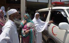 Relatives of a young Pakistani woman who died from injuries she suffered when set on fire stand by the ambulance carrying her body.