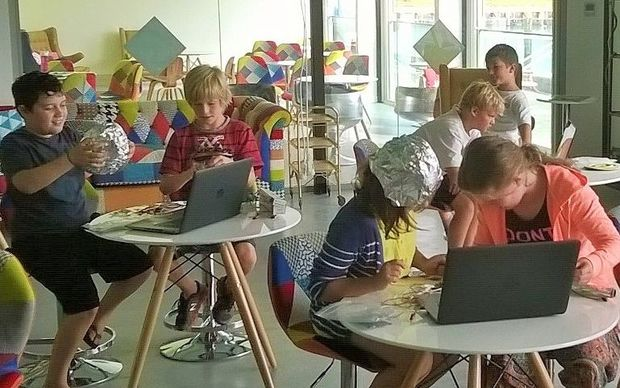Children sitting at tables with laptops