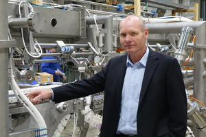 Andrew Arnold, General Manager of Robotics and Automation at Scott Technology, Dunedin stands in front of a large robotic processing machine made of a series of silver pipes