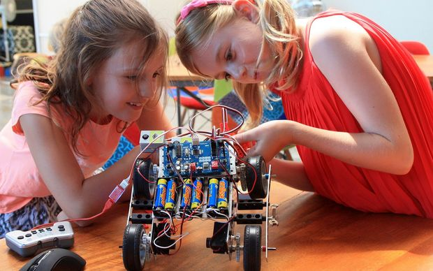 Two primary aged girls look at a robot on wheels on a  table