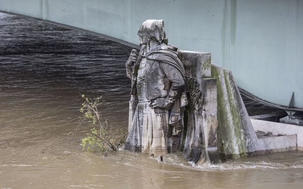 Floodwaters race past the Zouave statue at the Alma bridge on the River Seine, Paris. Floods in 1910 reached its shoulders.