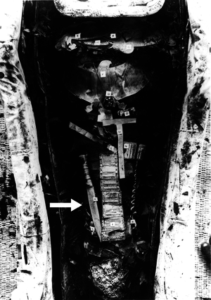 A black and white picture of the Tutankhamun mummy, showing the iron dagger (34.2 cm long) placed on the right thigh (arrowed).