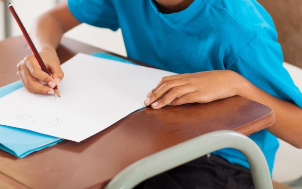 A young boy writes at a desk at a primary school.