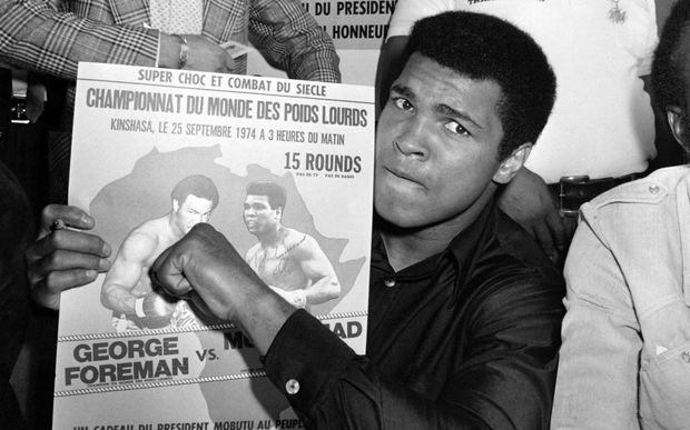 Muhammad Ali poses with a poster for his world heavyweight championship fight against titleholder US George Foreman which took place on 30 October 1974.