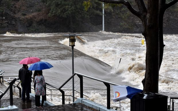 Residents watch the overflowing Parramatta river that submerged a ferry terminal in Sydney.