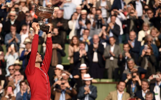 Novak Djokovic hoists the French Open trophy aloft in Paris
