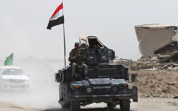 Iraqi government forces drive on a road near the village of al-Azraqiyah, northwest of the city of Fallujah, on June 5,