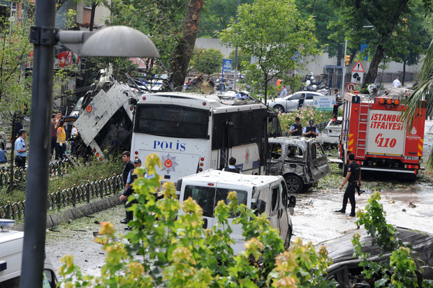 Police officers and rescuers inspect the site of a bomb attack that targeted a police bus in the Vezneciler district of Istanbul on 7 June 2016.