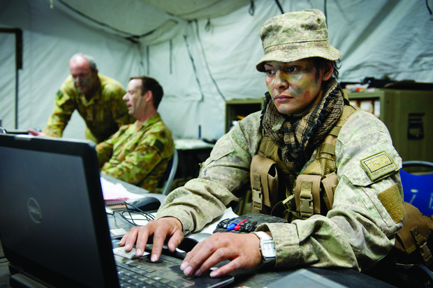 Member of the New Zealand Defence Force on a laptop in uniform