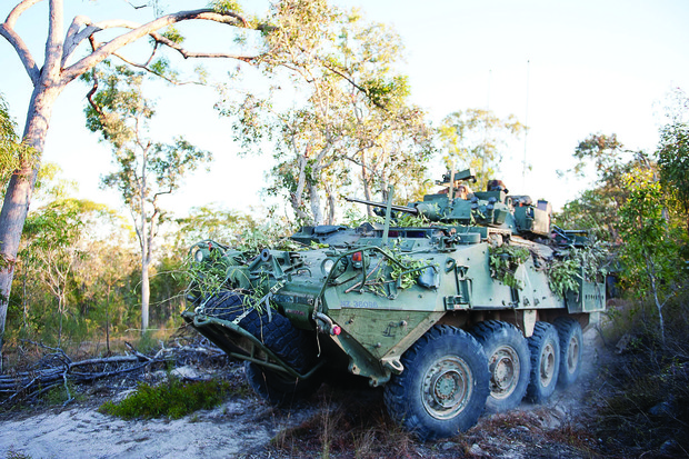 A New Zealand Defence Force tank driving through the bush.