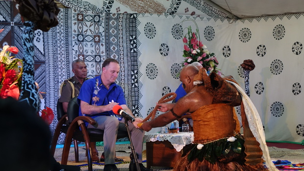 John Key receiving kava root.