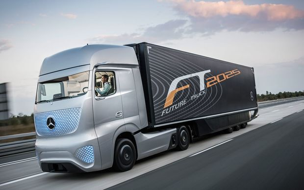 Futuristic looking truck with driver occupied on a laptop not steering vehicle