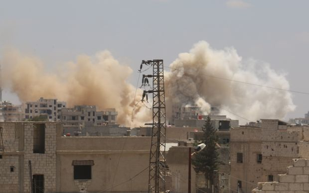 Smoke rises amid damaged buildings as the Assad regime forces carry out barrel bomb attack the opposition-controlled areas in the Darayya district in the southwest Damascus, Syria on June 10, 2016.