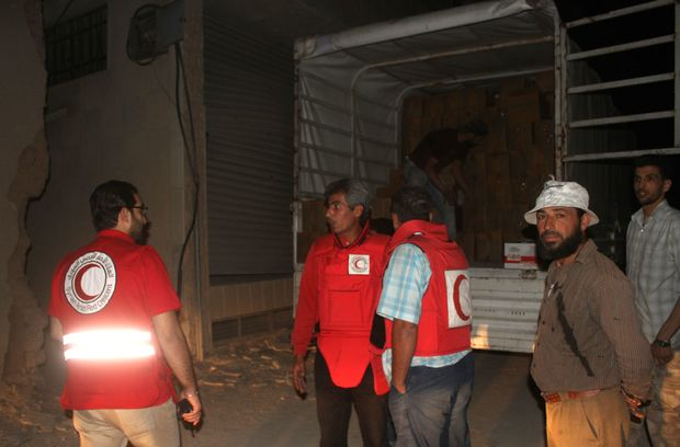 Members of the Syrian Arab Red Crescent unload a lorry after a UN and SARC aid convoy entered the Syrian rebel-held town of ‪Daraya