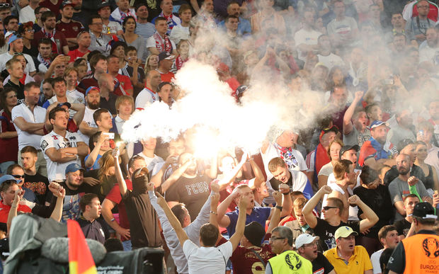 Football fans ignite flares during the UEFA Euro 2016 group stage match between the English and Russian national teams.