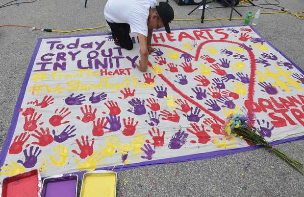 A man places a hand print on a makeshift memorial in a parking lot near the Pulse nightclub in Orlando, Florida on June 12, 2016.