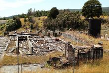 The remains of a demolished red brick building at Prohibition Mine in Waiuta, surrounded by grass and shrubs. The former mine on the West Coast is rated as the most toxic site in New Zealand