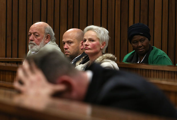 South African Paralympian Oscar Pistorius (Foreground) holds his head in his hands as members of Reeva Steenkamp's family including her father Barry Steenkamp(L), looks on during his resentencing hearing.