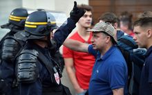 A football fan argues with riot police officers in central Lille.