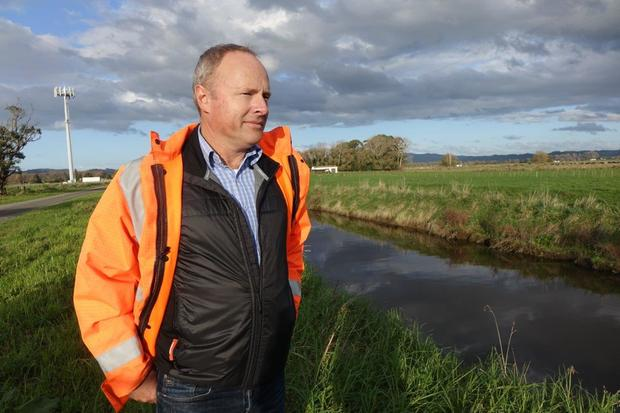 Brendon Love, the clean-up project manager at the Kopepepo Canal. Wearing a high-vis jacket he stands on the banks of the canal on a cloudy day