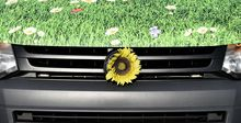 "A sunflower decorates a ""green"" VW electric car at a service station in Berlin."