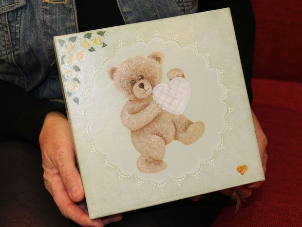 A photo of a memory box, a wooden box with a teddy bear on it. Karlena Kelliher makes them for parents who have lost an infant.