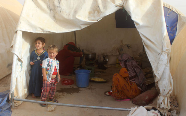 Displaced Iraqis from the embattled city of Fallujah cook at a camp where they are taking shelter some 18 kilometres from Ramadi on June 18, 2016.