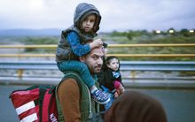A refugee carries a child as he walks to board a bus after crossing the Greek-Macedonian border.