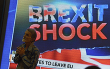 An Indian pedestrian gestures as he stands near a large screen showing news of Britain's vote to exit the European Union in Mumbai on 24 June 2016.