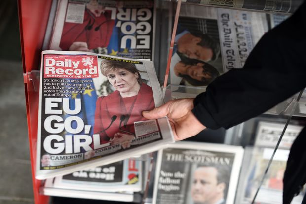 A man takes a copy of the Daily Record newspaper reporting on the pro-Brexit result of the UK's EU referendum vote and with an image of Scotland's First Minister and Leader of the Scottish National Party (SNP),