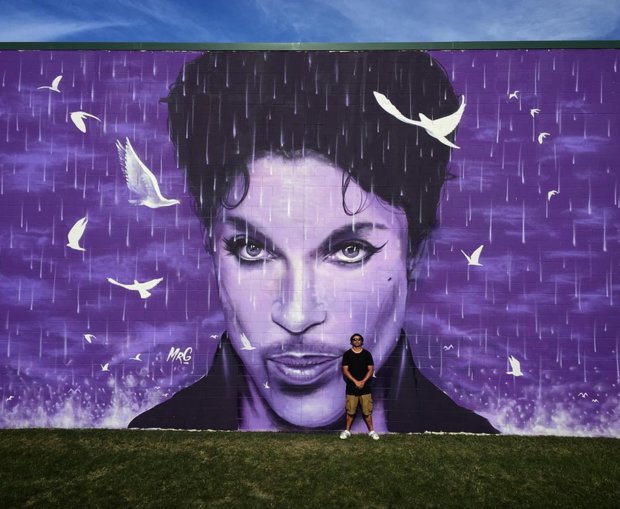 Artist Graham Hoete with his massive Prince wall mural.