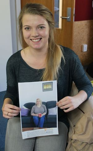 A photo of Brooke Gray with one of the images from her herstory photography project