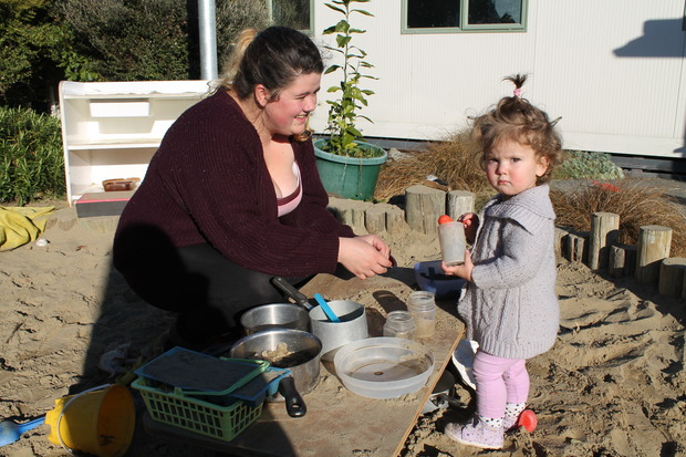 A photo of a young mother, Courtney Watts and her daughter, Sophia in the creche sandpit
