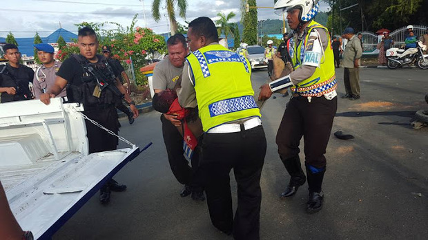 Indonesian police and security forces gather the body of West Papuan teenager Owen Pekei.