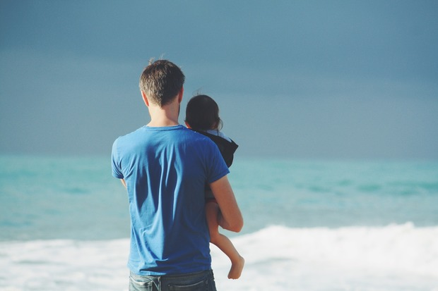 Father and child walk along the beach