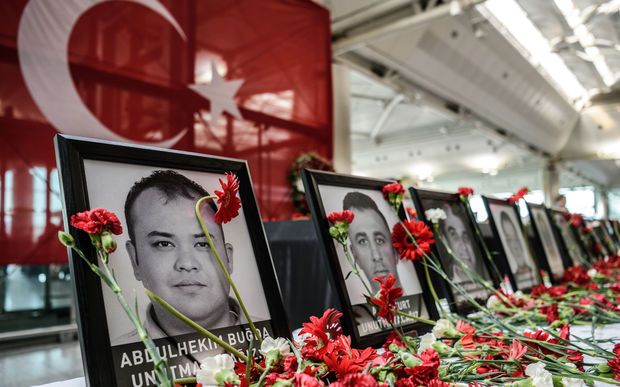 This picture taken on June 30, 2016 shows cloves left by airport employees next to killed airport employees pictures at Ataturk airport international terminal in Istanbul on June 30,