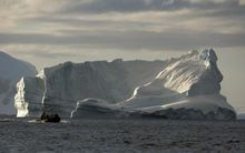 Tourists cruise alongside icebergs in the western Antarctic peninsula.