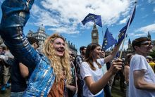 Marchers wave EU flags in London's Parliament Square as thousands protest against Britain's vote to leave the union.